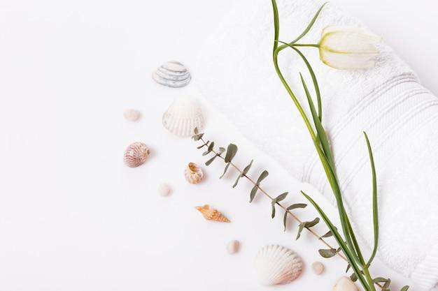 Koncepcja spa. delikatny biały kwiat, świeczki, muszle, kamienie, białe ręczniki tło wiosenne lub letnie