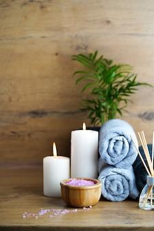 Koncepcja spa i aromaterapii świece, ręczniki, różowa sól morska i aromatyczny dyfuzor z trzciny na drewnianym stole.