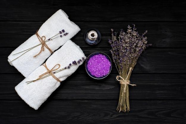 Koncepcja spa. lawendowa sól do relaksującej kąpieli, aromatyczny olej, białe ręczniki i suche kwiaty lawendy na czarnym drewnianym tle. aromaterapia leżał płasko.