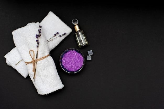 Koncepcja spa. lawendowa sól do relaksującej kąpieli, aromatyczny olej, białe ręczniki i suche kwiaty lawendy na czarnym tle. aromaterapia leżał płasko.
