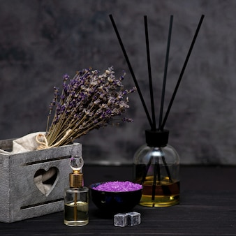 Koncepcja spa. lawendowa sól do relaksującej kąpieli, aromatyczny olej, suszone kwiaty lawendy, perfumy na szarym tle. aromaterapia