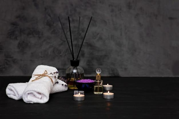 Koncepcja spa. lawendowa sól do relaksującej kąpieli, aromatyczny olej, świece, białe ręczniki, suche kwiaty lawendy, perfumy na szarym tle. aromaterapia