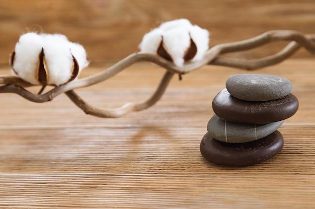 Koncepcja spa. puszyste bawełniane kwiaty i duże płaskie kamienie na naturalnym rustykalnym drewnianym tle.