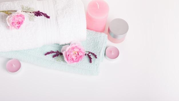 Koncepcja spa w walentynki, urodziny, dzień matki, różowe róże, świece, niebieskie ręczniki, kwiaty. tło wiosna lub lato