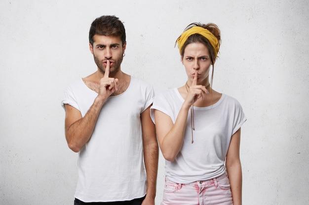 Koncepcja spisku. młody mężczyzna i kobieta ubrany niedbale, trzymając palce na ustach, prosząc o milczenie na białym tle
