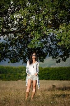 Koncepcja spokoju ducha wolności. atrakcyjna młoda kobieta idzie w polu. nie może się doczekać z lekkim uśmiechem.
