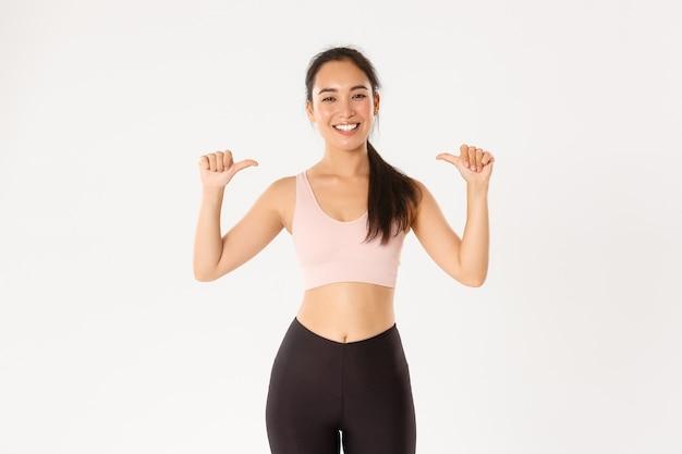 Koncepcja sportu, dobrego samopoczucia i aktywnego stylu życia. dumna i szczęśliwa uśmiechnięta azjatycka instruktorka fitness, sportsmenka wskazująca na siebie, osiągająca cel treningu, zostaje członkiem siłowni, biała ściana.