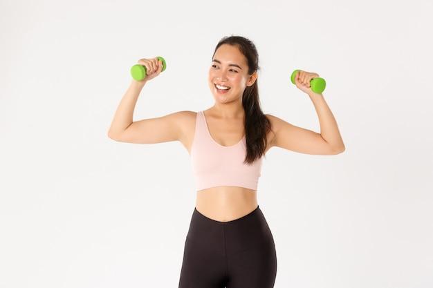 Koncepcja sportu, dobrego samopoczucia i aktywnego stylu życia. podekscytowana i szczęśliwa szczupła, urocza azjatycka dziewczyna podnosi hantle na zajęciach fitness, ciesząc się treningiem, postępuj zgodnie z zaleceniami trenera online, biała ściana