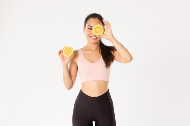 Koncepcja sportu, dobrego samopoczucia i aktywnego stylu życia. portret uśmiechniętej zdrowej i szczupłej azjatki radzi jeść zdrową żywność na śniadanie, nabrać energii do treningu, trzymać dwie połówki pomarańczy.