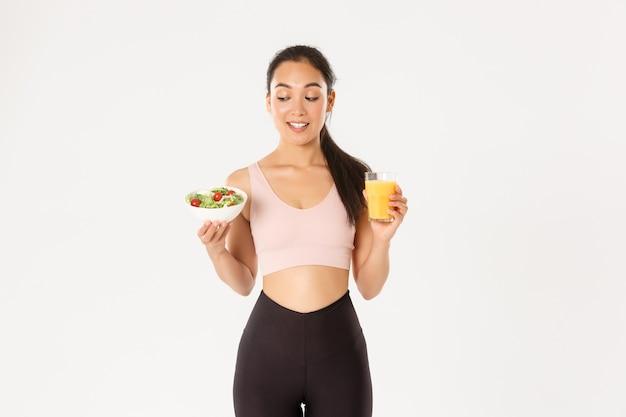 Koncepcja sportu, dobrego samopoczucia i aktywnego stylu życia. uśmiechnięta zdrowa i szczupła brunetka azjatycka dziewczyna jak fitness, chodzenie na siłownię i bycie na diecie, trzymając sałatkę z sokiem pomarańczowym, stojąc na białym tle