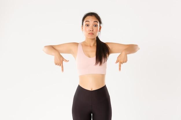 Koncepcja sportu, dobrego samopoczucia i aktywnego stylu życia. zaskoczona i pod wrażeniem azjatycka fitness dziewczyna, siłownia lub sportsmenka w odzieży sportowej, wskazująca palcami w dół, wyglądająca na oniemiałego, białe tło.