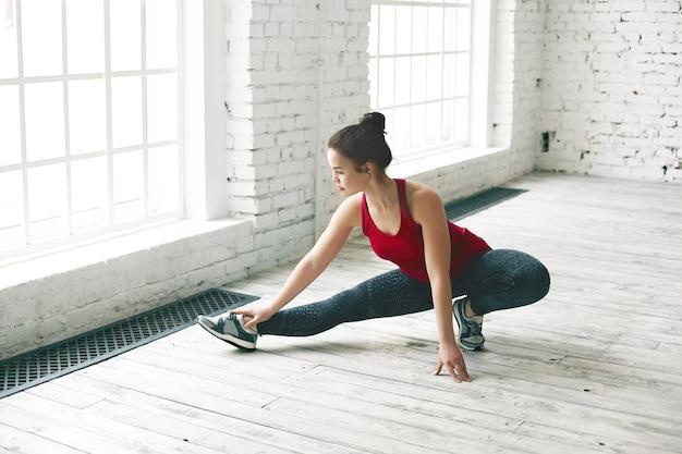 Koncepcja sportu, fitness i aktywności. atletyczna, umięśniona brunetka dziewczyna w trampkach, legginsach i podkoszulku, ćwiczy w centrum siłowni, rozciągając nogi na drewnianej podłodze, o poważnym, skupionym spojrzeniu