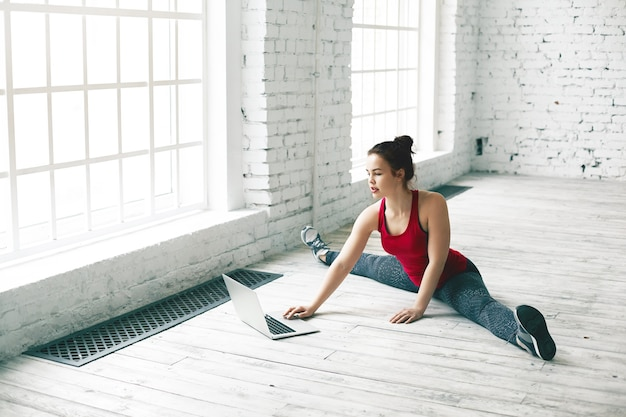Koncepcja sportu, fitness i nowoczesnych technologii. kobieta ćwiczy szczeliny boczne na podłodze i jednocześnie sprawdza pocztę na otwartym komputerze przed nią