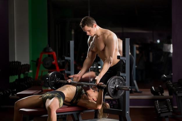 Koncepcja sportu, fitness, pracy zespołowej, kulturystyki i ludzi - młoda kobieta i osobisty trener ze sztangą napinającą mięśnie w siłowni