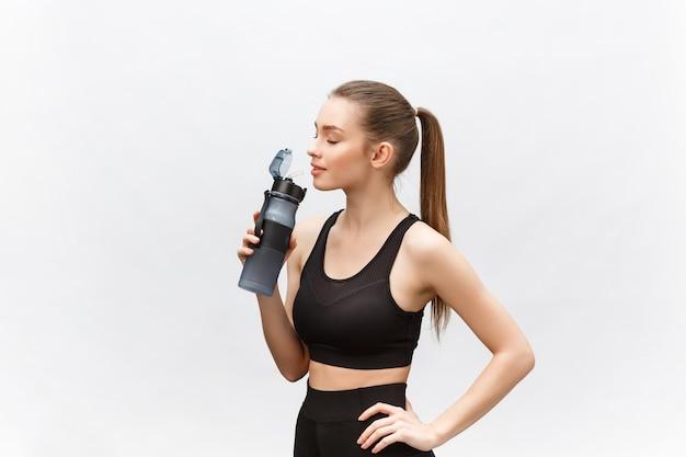 Koncepcja sportu, fitness, stylu życia i ludzi - szczęśliwa kobieta sprawny z butelkami wody.
