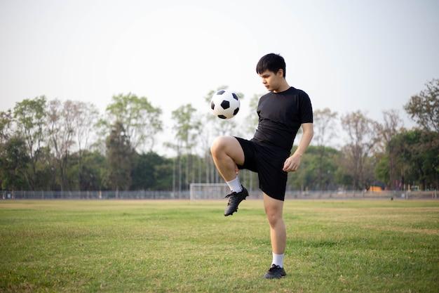 Koncepcja sportu i rekreacji męski piłkarz ubrany w czarną koszulkę i spodnie uprawiający kopanie piłki na trawiastym boisku.