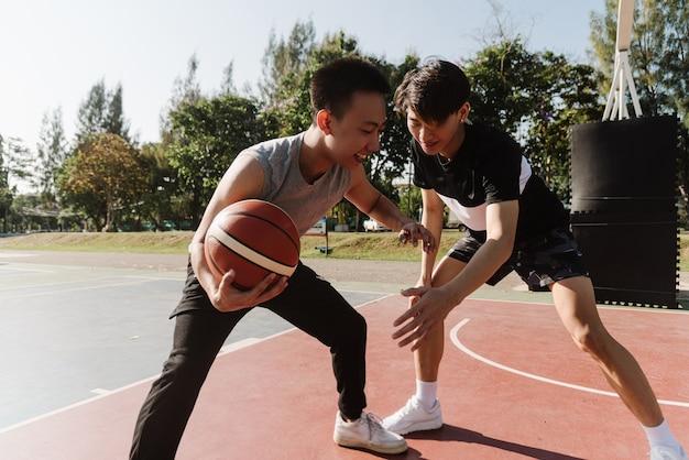 Koncepcja sportu i rekreacji młodych nastolatków płci męskiej uprawiania koszykówki dryblingu na boisku po szkole.
