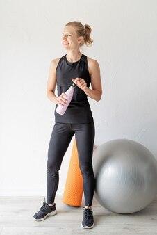 Koncepcja sportu i zdrowego stylu życia. portret młodej wysportowanej kobiety wody pitnej po treningu z fitball
