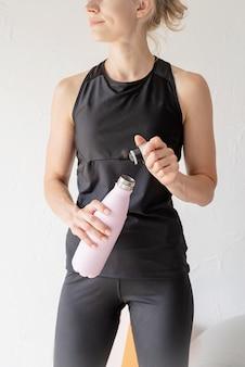 Koncepcja sportu i zdrowego stylu życia. zbliżenie na ręce kobiety trzymającej butelkę termosu