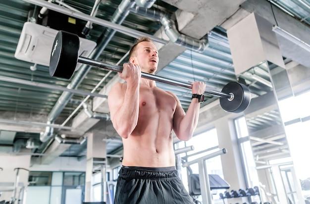 Koncepcja sportu, kulturystyki, stylu życia i ludzi - młody człowiek ze sztangą wyginanie mięśni w siłowni. zdjęcie poziome