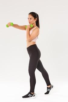 Koncepcja sportu, siłowni i zdrowego ciała. pełna długość skoncentrowanej athelte, azjatyckiej brunetki wykonującej ćwiczenia fitness, treningu z hantlami, produktywnego treningu na siłowni na białym tle.