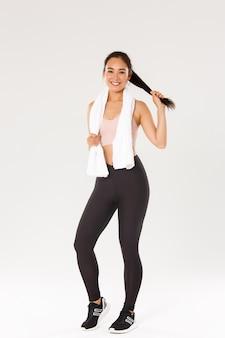 Koncepcja sportu, siłowni i zdrowego ciała. pełna długość zdrowej i aktywnej, uśmiechniętej azjatyckiej fitness dziewczyny, brunetki lekkoatletki, ocierającej pot ręcznikiem po dobrym treningu, trening na siłowni.