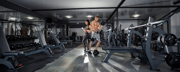 Koncepcja sportu, treningu, fitness, stylu życia i ludzi - młoda kobieta z osobistym trenerem, wyginając mięśnie pleców i brzucha na ławce w siłowni. zdjęcie wysokiej jakości