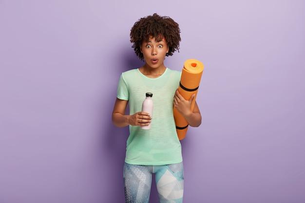 Koncepcja sportu. zszokowany fitness kobieta trzyma walcowane karemat, butelka z wodą