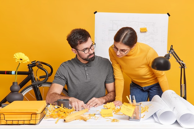 Koncepcja spotkania i współpracy podczas burzy mózgów. uważne kursy nauki kobiet i mężczyzn w zakresie nowoczesnych prac biurowych nad wspólną pozą projektową na pulpicie skupiły się na wyrażeniach na papierach