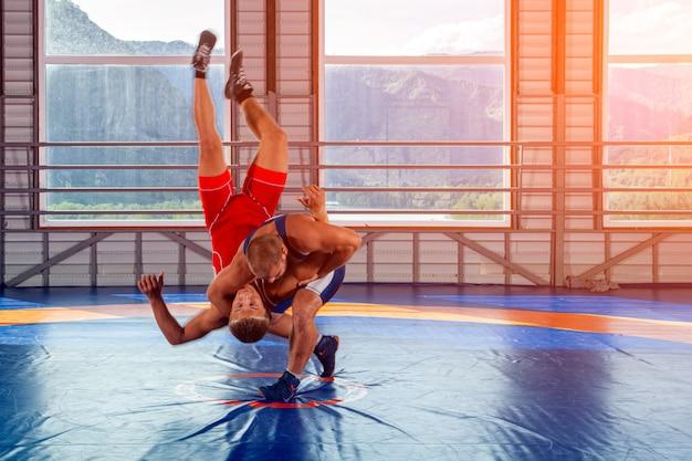 Koncepcja sprawiedliwego zapaśnictwa. dwóch grecko-rzymskich zapaśników w czerwonym i niebieskim mundurze, tworzących super zapasy na dywanie zapaśniczym na siłowni. koncepcja męskiego zapaśnictwa i oporu