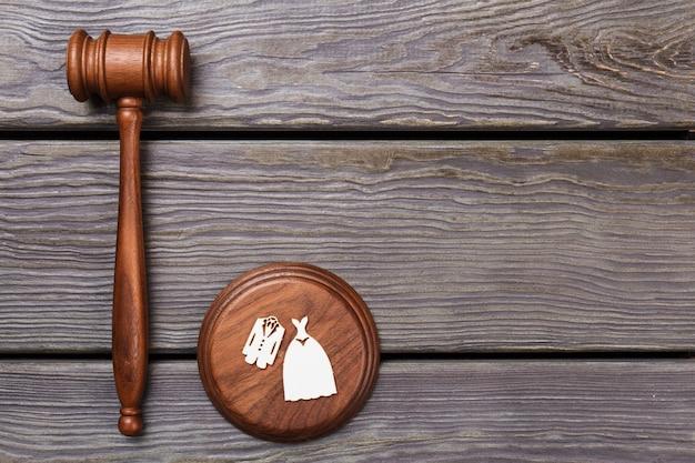 Koncepcja sprawiedliwości małżeństwa. drewniany młotek i blok dźwiękowy z kostiumami ślubnymi.