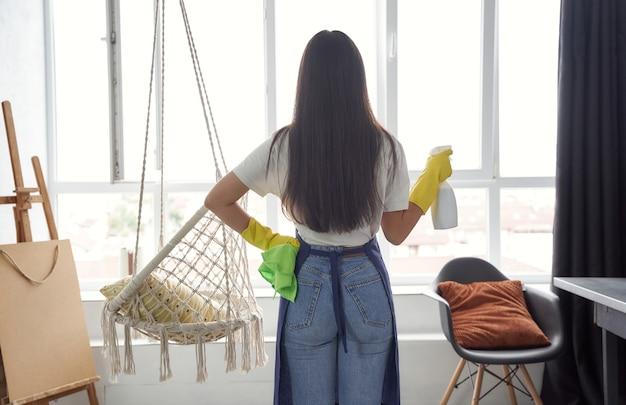 Koncepcja sprzątania i sprzątania widok z tyłu młodej kobiety sprzątającej w kolorze żółtym