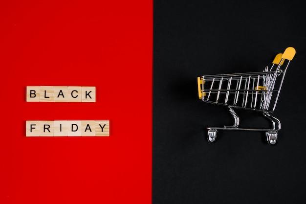 Koncepcja sprzedaży czarny piątek. mini koszyk i znak na czerwonym tle. baner reklamowy.