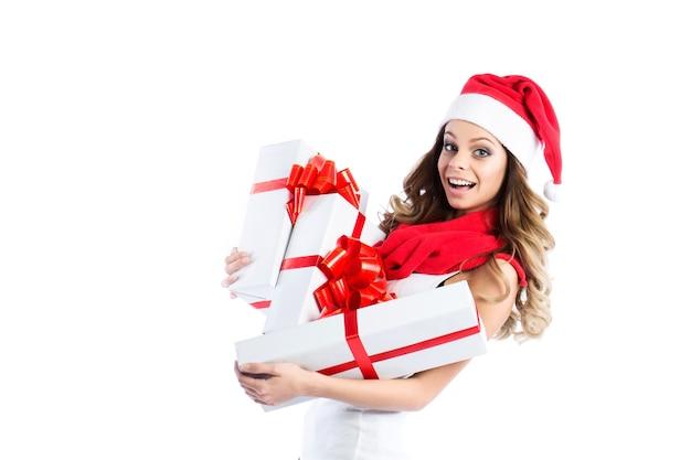 Koncepcja sprzedaży i świąteczne zakupy. wesoła kobieta w santa kapelusze uśmiechnięte prezenty gospodarstwa na białym tle.