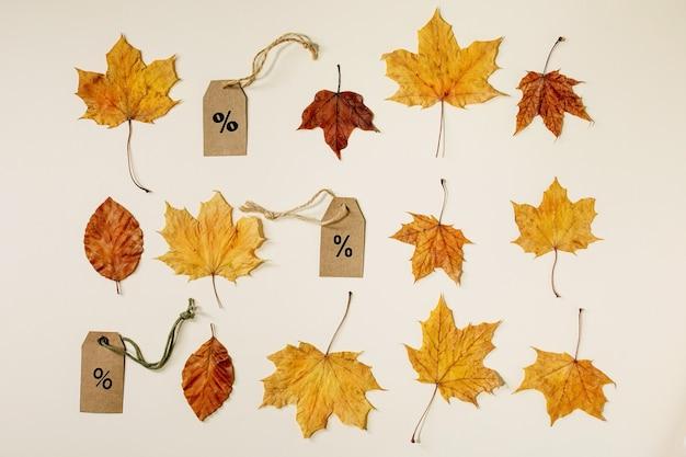 Koncepcja sprzedaży jesienią. etykiety kartonowe z procentami, różne żółte jesienne liście w rzędzie na beżowym tle. leżał na płasko.