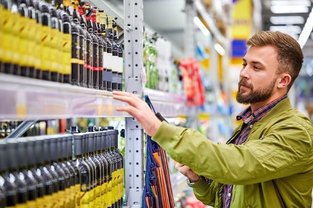 Koncepcja sprzedaży, konsumpcjonizmu, alkoholu i ludzi - młody człowiek z butelką wina, wybierz najlepszy i pyszny, spójrz na półkę
