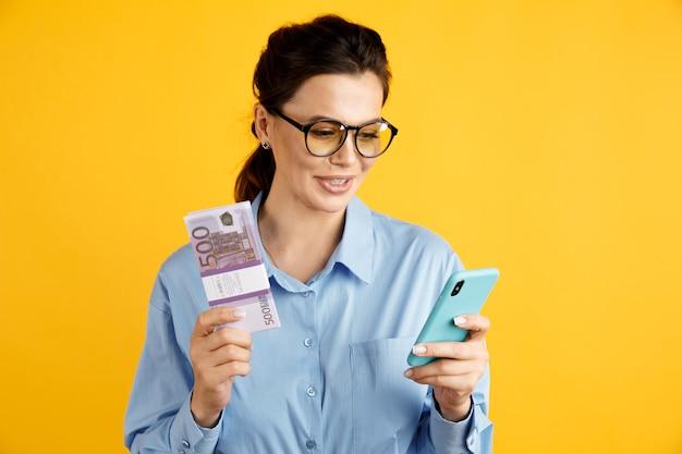 Koncepcja sprzedaży online. elegancki bizneswoman z pieniędzmi i telefonem