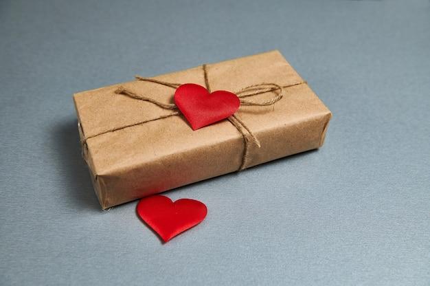 Koncepcja st valentines day. prezent na walentynki z ekologicznego papieru i czerwonych serc na szarym tle