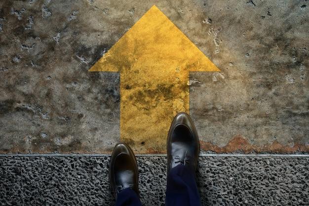 Koncepcja startu i wyzwania. biznesmen w formalnych butach kroki, aby podążać za żółtą strzałką, przygotować się do posuwania się naprzód lub zaryzykować sukces. widok z góry