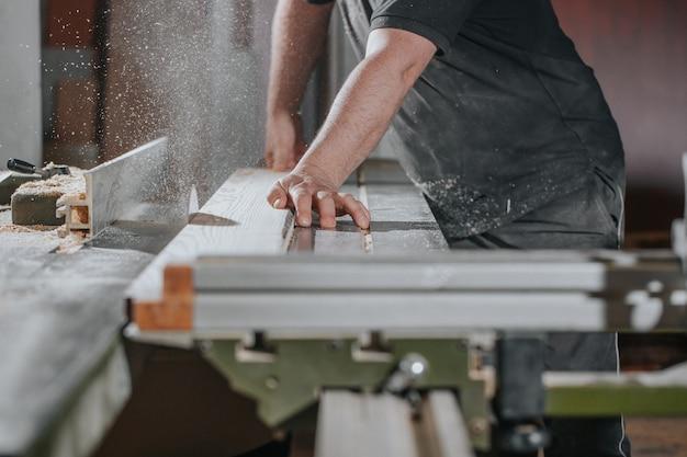 Koncepcja stolarki budowlanej i stolarskiej profesjonalny stolarz stolarski wykonujący piłowanie mebli rzemieślniczych lub manufakturowych