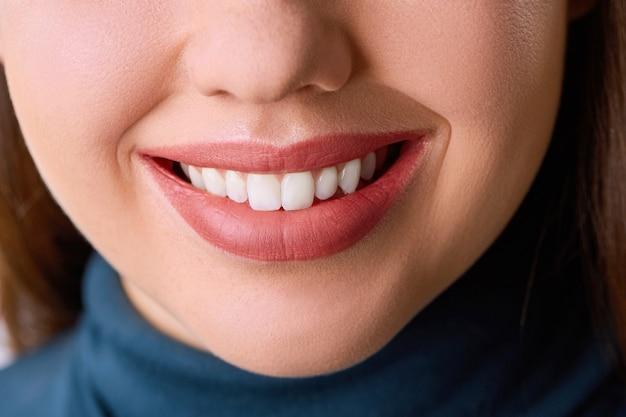 Koncepcja stomatologii, portret dziewczyny z mocnymi białymi zębami i uśmiechnięty.
