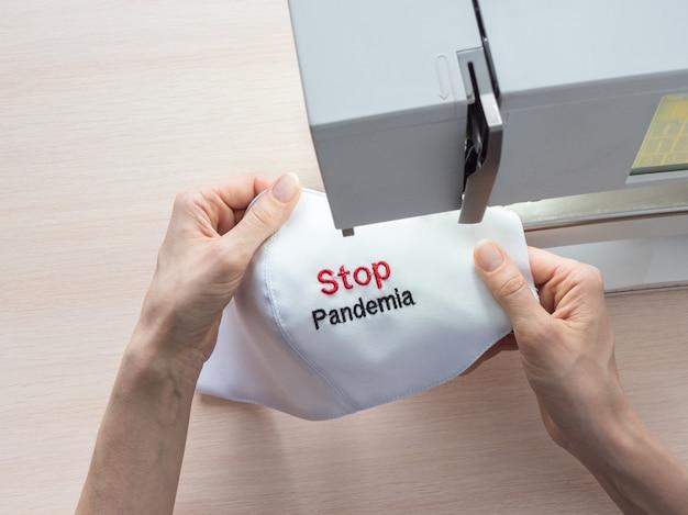 Koncepcja stop pandemia. wykonywanie w domu masek ochronnych. maszyna do szycia w procesie produkcyjnym. produkcja do ochrony przed pandemią przeciwko covid-19