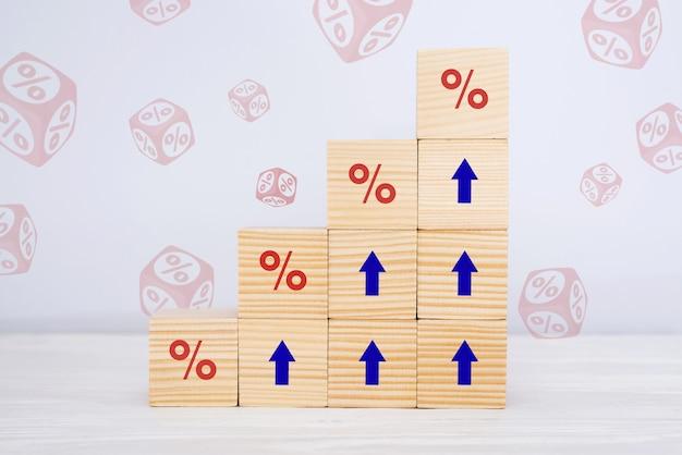 Koncepcja stóp procentowych finansowych i hipotecznych. drewniane kostki rosnące w górę, z ikoną symbolu procentu, strzałkami skierowanymi w górę
