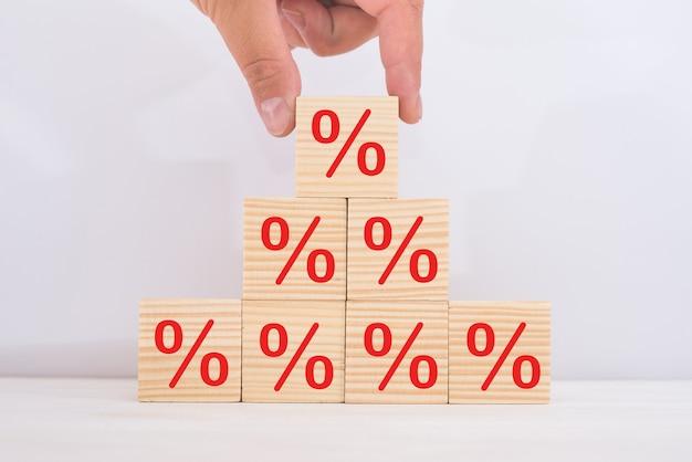 Koncepcja stóp procentowych finansowych i hipotecznych. ręczne kładzenie drewnianego sześcianu zwiększającego się na górze z symbolem procentu ikony w górę