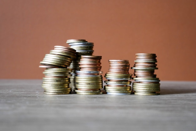 Koncepcja stosu monet pozwala zaoszczędzić pieniądze. monety na brązowym tle