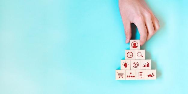 Koncepcja strategii biznesowej i planu działania. ręka trzyma blok drewna kostki układania z ikoną