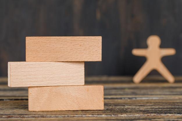 Koncepcja strategii biznesowej z drewnianymi klockami, ludzka postać na drewnianym stole widok z boku.