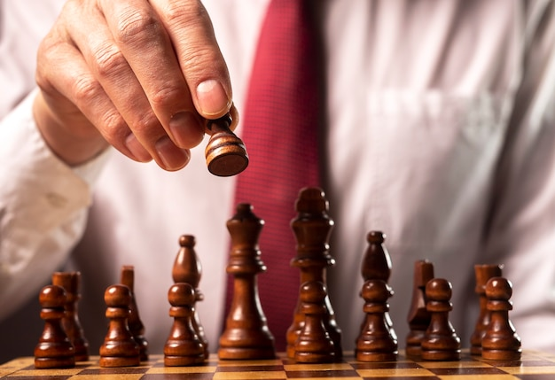 Koncepcja strategii finansowej firmy. biznesmen podejmowania decyzji i przesuwania figury szachowej nad innymi figurami szachowymi.