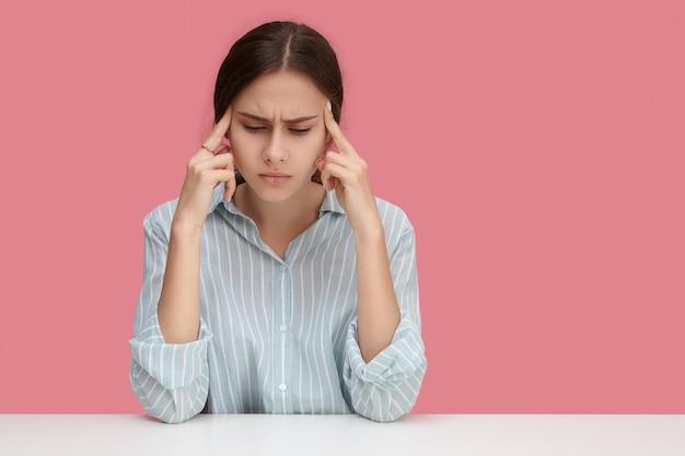 Koncepcja stresu, zdrowia, choroby i problemów. przygnębiona sfrustrowana młoda bizneswoman mająca straszny ból głowy, zestresowana z powodu problemów finansowych, masująca skronie