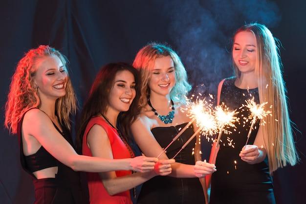 Koncepcja strony noworoczne, uroczystości i święta - młode wesołe kobiety trzymające płonące ognie.